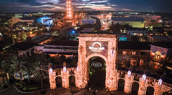 The entrance to Universal Studios Orlando is lit up at night during Halloween.