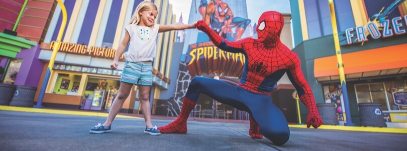 A girl fist bumps Spider-Man. Text: Universal's Islands of Adventure.