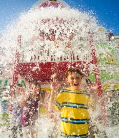 Water pours down on a group of children at the Curious George Goes to Town play area.
