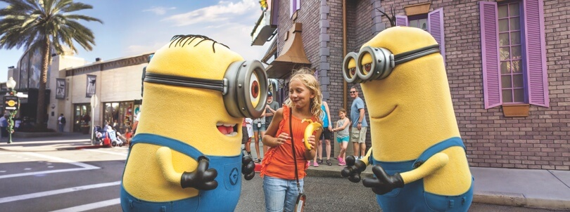 Little girl smiling as she meets two Minions from the Despicable Me Minion Mayhem 3D ride at Universal Orlando.