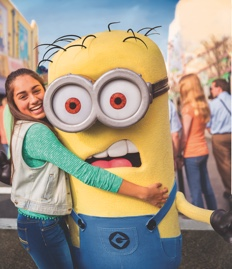A girl hugs a Minion making a silly face at Universal Studios Florida.