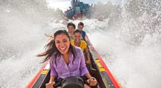A group of young adults splashes through Dudley Do Right's Ripsaw Falls at Universal Orlando's Toon Lagoon.