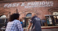 Guests at Universal Studios Florida head toward the Fast & Furious Supercharged ride entrance, a large industrial looking brick building.