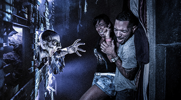Guests scream and cringe as a creature bursts through a wall at them during Halloween Horror Nights in Orlando.