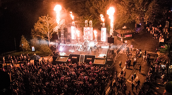 An overhead shot of a crowd gathered before a stage filled with dancers and fire effects during Halloween Horror Nights.