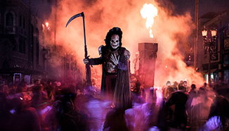 A hooded skeleton reaper beckons from a crowd at Universal's Halloween Horror Nights.