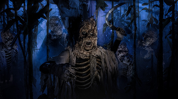 At Universal's Halloween Horror Nights, a decaying skeleton wielding a scythe lurks in the shadows.