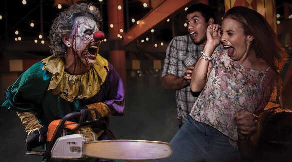 A clown with a chainsaw lunges at a terrified couple in a Halloween Horror Nights scare zone.