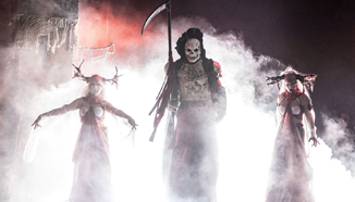 Three spooky figures on stilts emerge from the fog at Halloween Horror Nights.