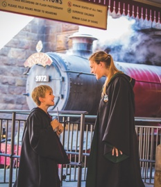 Two children wearing wizard robes queue in front of the Hogwarts Express at Hogsmeade Station.