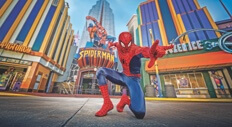 The Spider-Man character poses in front of the Spider-Man ride. Text: Universal's Islands of Adventure.