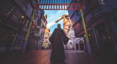 A girl with a wizard's robe and wand walks down the streets of Diagon Alley, part of the Wizarding World of Harry Potter at Universal Studios Orlando.