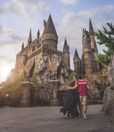 A father and son walk toward the Hogwarts castle in the Wizarding World of Harry Potter - Hogsmeade.